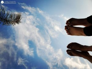 Looking up at feet of mother and daughter against a background of clouds in the sky